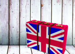 56292578 - great britain flag suitcase against wooden table
